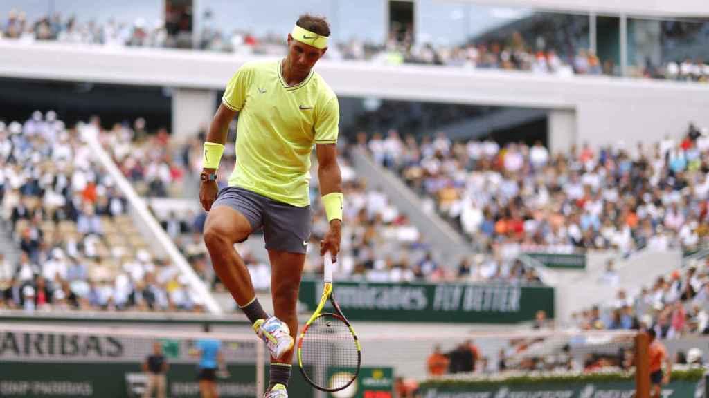Rafael Nadal golpea sus zapatillas para retirar la tierra pegada a ellas
