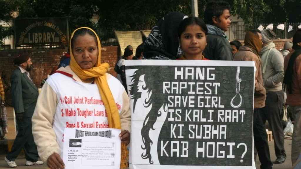 Dos mujeres piden pena de muerte para los violadores durante una protestas en la India. Se puede leer: Colgar al violador salva a la chica.