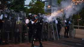 Policías hongkoneses disparan gases lacrimógenos contra protestantes.