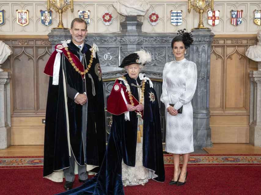 El rey Felipe, la reina Isabel II de Inglaterra y la reina Letizia, con vestido de la firma sevillana Cherubina.