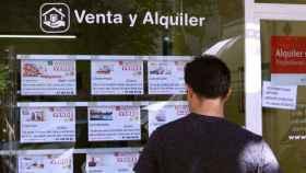 Una persona mirando el cartel de una agencia inmobiliaria en una imagen de archivo.