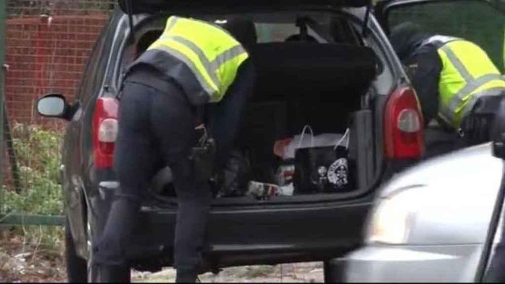 Agentes buscando en un maletero.