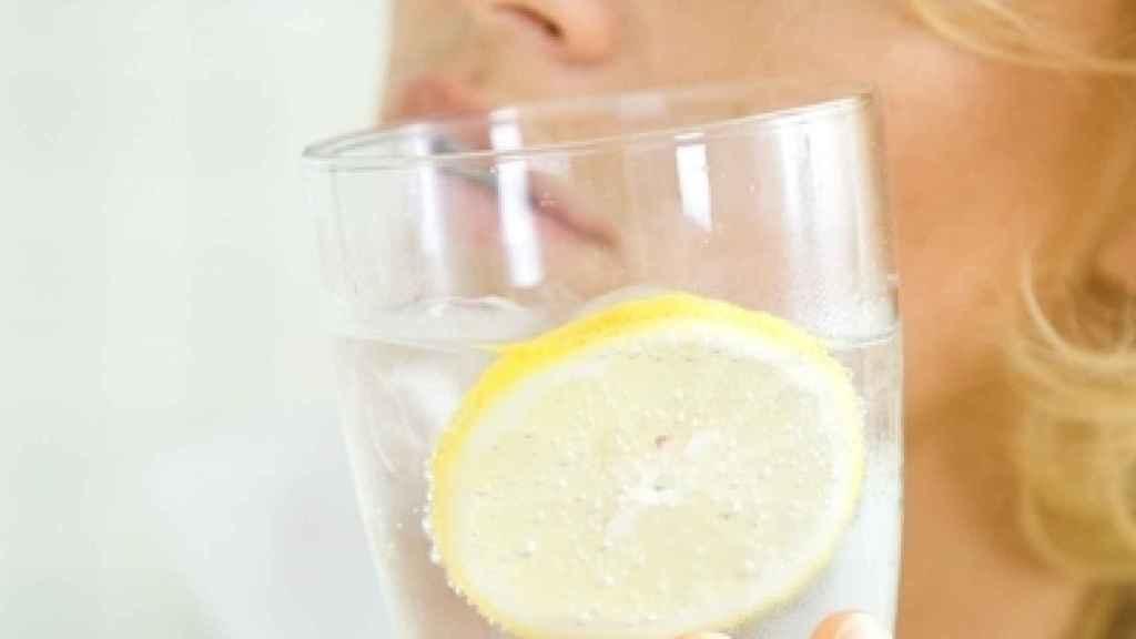 Una mujer sostiene un vaso de agua con gas