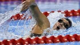 Una nadadora compitiendo en una piscina olímpica.