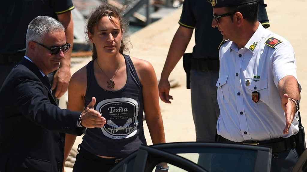 Carola Rackete, capitana del Sea Watch, desembarca acompañada por un policía.