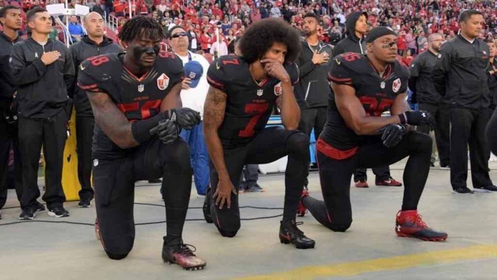 Colin Kaepernick (en el medio) arrodillado durante el himno.