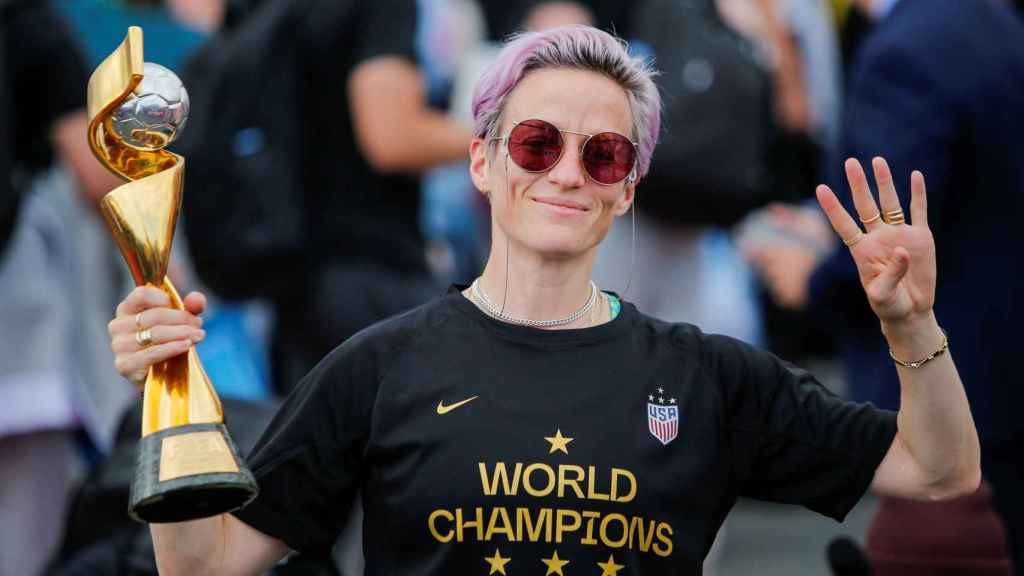 Megan Rapinoe gestures the number 4 with her fingers as she holds the Trophy for the FIFA Women's World Cup while the U.S. team arrives at the Newark International Airport, in Newark