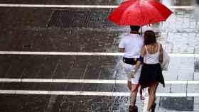 Dos personas se protegen de la lluvia en una de las céntricas calles de Pamplona. EFE/ Javier Lizón