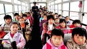 Un grupo de niños chinos de camino al colegio en un autobús escolar.