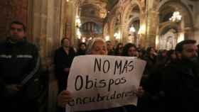 Una manifestane sosteniendo un letrero durante una misa en Santiago de Chile.
