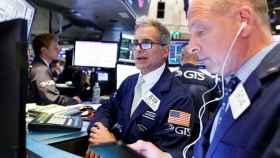 Dos brókeres consultan pantallas en Wall Street.