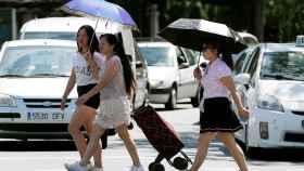 Tres mujeres se protegen del sol y del calor con sombrillas en Valencia. EFE/Kai Försterling