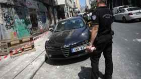 Un policía, junto a un coche dañado por el terremoto que se ha producido este viernes en Atenas.