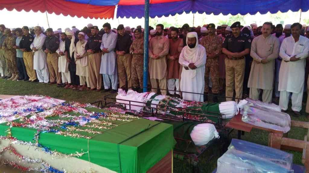 Poilicáis, soldados y allegados a las víctimas rezan ante sus cuerpos en Dera Ismail Khan (Pakistán).