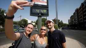 Unos turistas se fotografían con un termómetro del centro de Córdoba que indica 44 grados. EFE/ Salas.