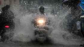 Una moto atraviesa una balsa de agua.