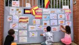 La puerta del colegio se llenó de banderas de España en apoyo a la niña.