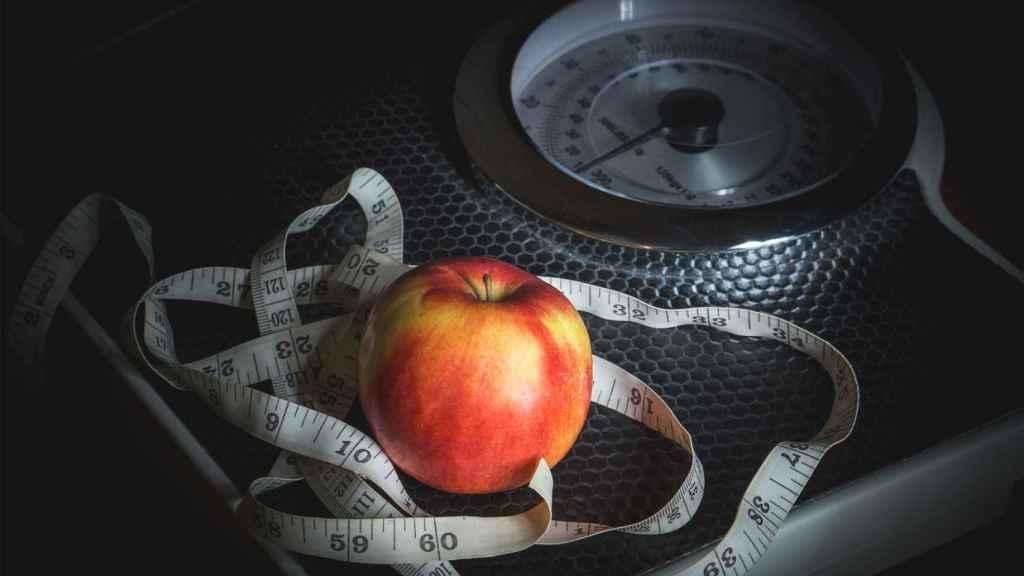 Una cinta métrica y una manzana sobre una báscula.