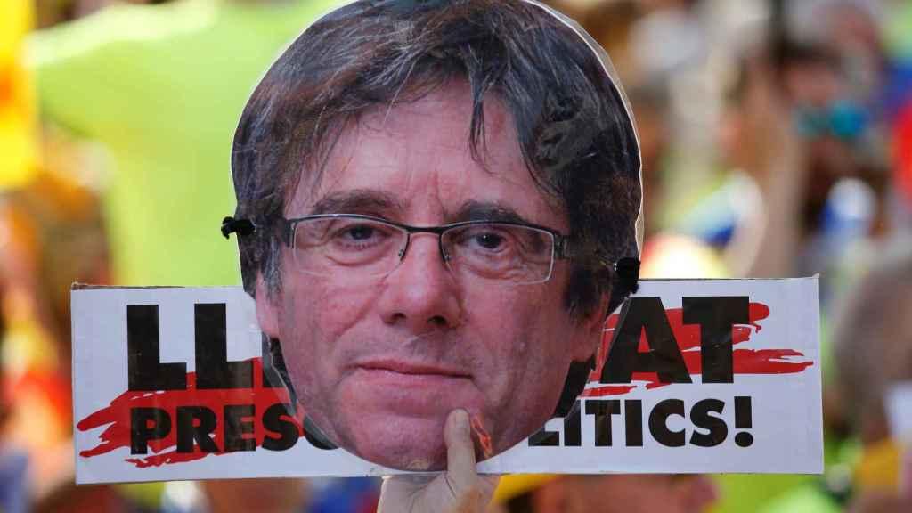 Una pancarta pidiendo la libertad de los políticos presos junto a una máscara de Puigdemont.