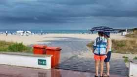 Dos mujeres se resguardan de la lluvia en una playa de Menorca / David Arquimbau Sintes. EFE