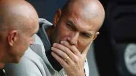 Zinedine Zidane habla con uno de sus ayudantes en el banquillo