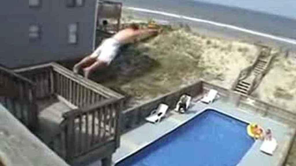 Un joven se lanza desde un balcón a una piscina.