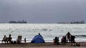 Varios personas disfrutan de un día de playa en Pinedo de Valéncia.