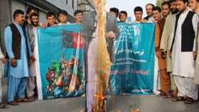 Varios afganos queman un retrato de Donald Trump.