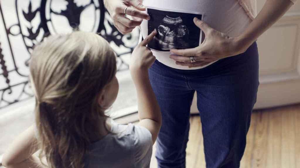 Una mujer embarazada con una ecografía de su bebé.