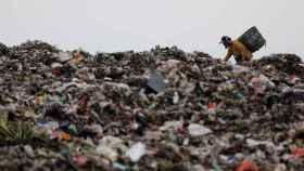 Un hombre busca plástico en una montaña de residuos en Indonesia.