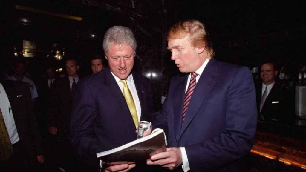 Trump le enseña un libro a Clinton en junio del año 2000.