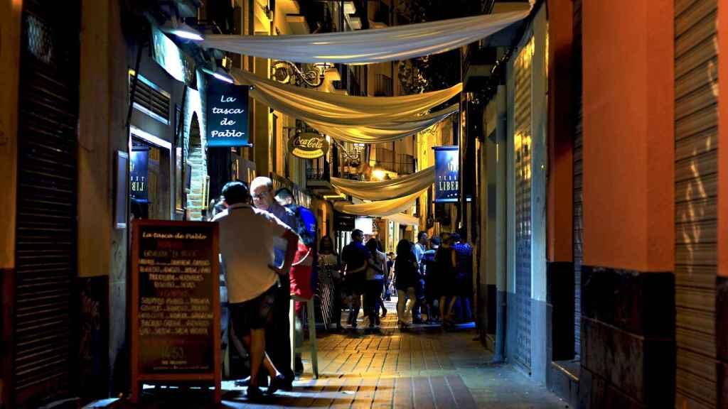 Una zona de bares, por la noche.