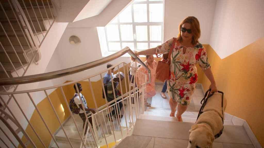 La lectora ciega, agarrada a su perra, subiendo a la segunda planta de la biblioteca municipal para impartir su clase.