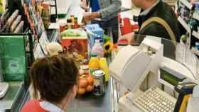 Una mujer pagando en el supermercado.