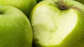 Una manzana verde con un mordisco en su parte exterior.