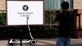 Man takes pictures of a semi-autonomous scooter KickScooter T60 that can return itself to charging stations without a driver, at a Segway-Ninebot product launch event in Beijing