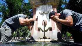 Unos turistas se refrescan en una fuente de Córdoba.