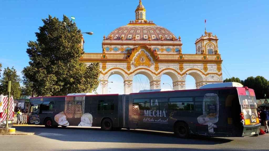 Un autobús con publicidad de La Mechá, frente a la puerta de la Feria de Abril.