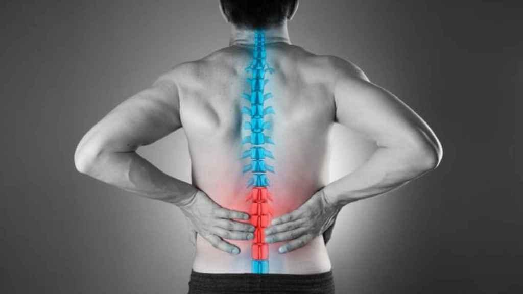 Un hombre se echa mano a las lumbares por un dolor en la espalda.