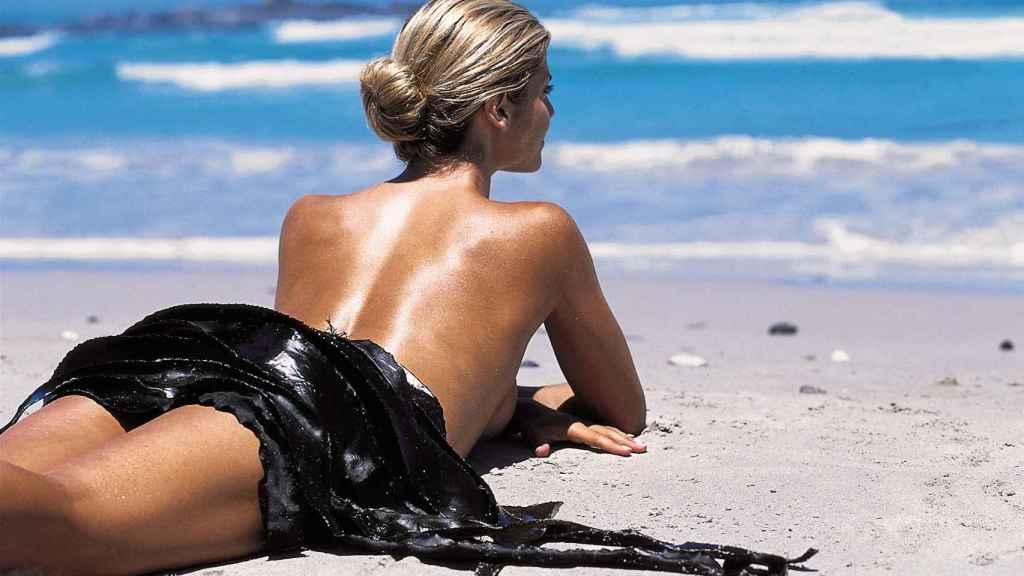 Una mujer desnuda en la playa.