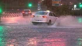 Un taxi atraviesa calles anegadas por las tormentas. EFE.