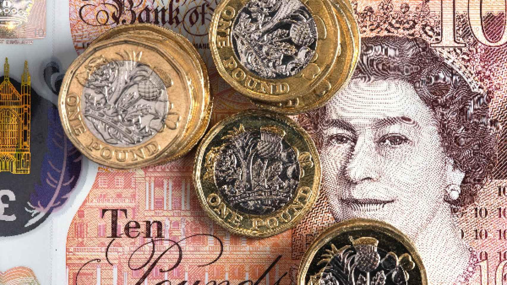 Un billete y monedas de libras esterlinas.