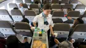 Una azafata atiende a los pasajeros de un avión.