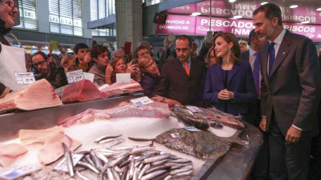 Los reyes Felipe y Letizia admiran pescados en un mercado de Valencia.