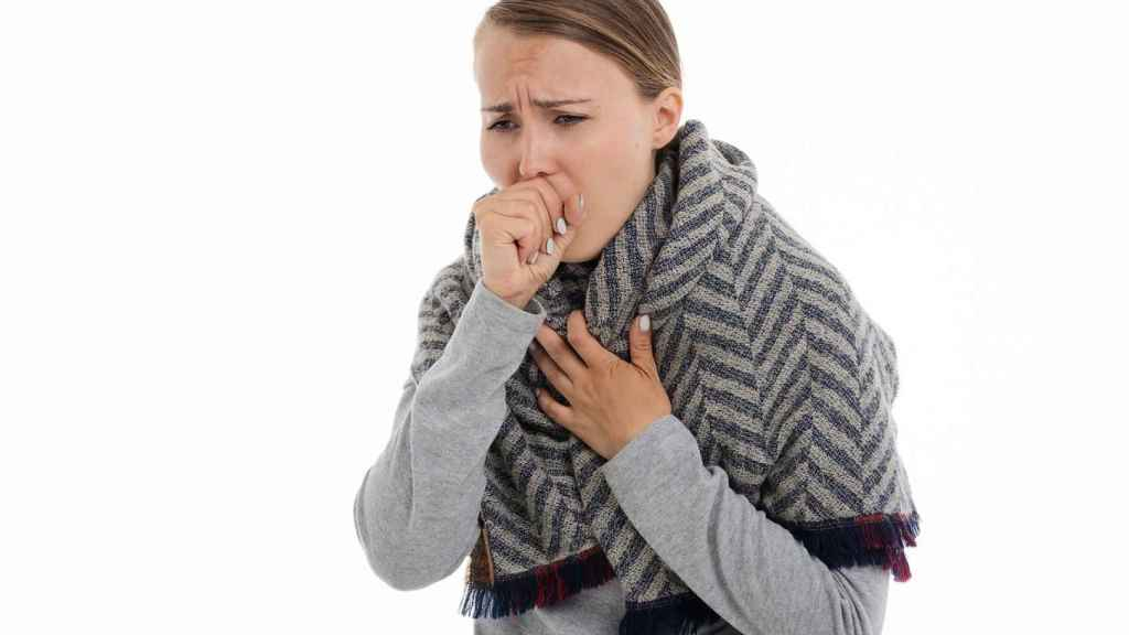 Una mujer tosiendo.