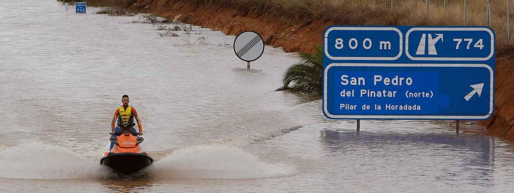 Un miembro de los servicios de rescate cruza en moto acuática la salida del túnel de la AP-7en Pilar de la Horadada (Alicante).