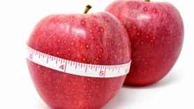 Una cinta métrica alrededor de una manzana roja.