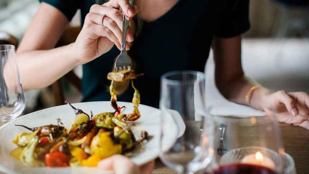 Una joven pinchando en un plato de verdura con un tenedor.