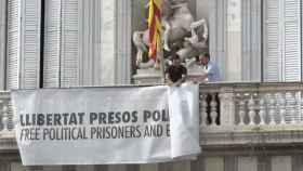 Momento en el que retiran la pancarta en apoyo a los políticos presos de la fachada de la Generalitat.