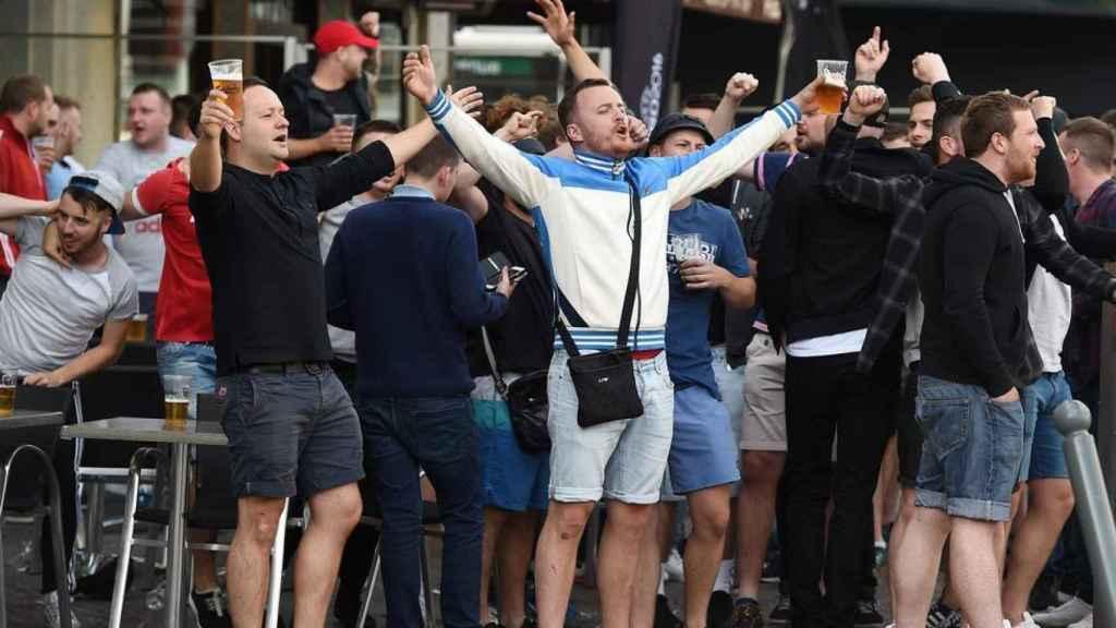 Aficionados ingleses cantando y bebiendo cerveza